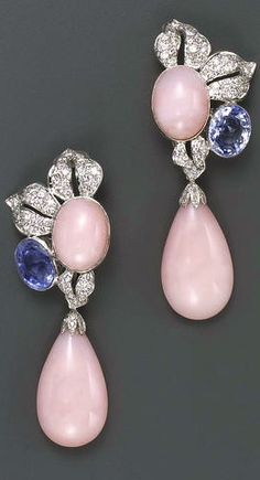 A pair of pink opal, sapphire, diamond and fourteen karat white gold pendant earrings each designed as a pavé-set diamond foliate cluster centering an oval cabochon pink opal and accented by an oval-shaped light blue sapphire, suspending a detachable pink opal drop; estimated total diamond weight for the pair: 3.50 carats; estimated total sapphire weight for the pair: 10.00 carats.