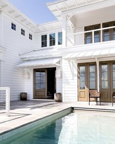 A picture perfect beach house for a #summerfriday afternoon. Shown here is our Baxter Wall #lantern in seashell white with hale navy accents and clear glass. Design by @cortneybishopdesign. #lighting #lightfixtures #urbanelectric #americanmade #theurbanelectricco #lights #exteriorlights #curbappeal