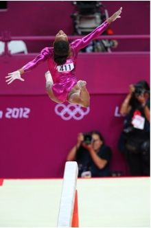 406d: This image again glorifies US favorite, Gabby Douglass.  She's mid-air and her position looks perfect, making her seem like a perfect athlete.  She also looks so focused on her performance that she is almost somewhere else.