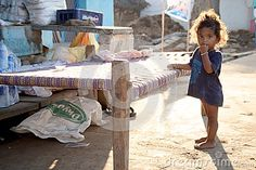 Small girl leaning against the bed outdoors in a village, India, ahobilam, Andhra