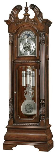 """Howard Miller Stratford 611-132 Grandfather Clock  This handsome floor clock features a stepped swan neck pediment with book matched olive ash burl, a carved finial, rosettes and a decorative vine and shell overlay.   The brushed nickel dial features corner and center ornaments, and includes a silver chapter ring with applied satin black Arabic numerals.   Cable-driven, Triple chime Kieninger movement offers automatic nighttime chime shut-off option.  Size: H. 93-1/4"""" W. 29-3/4"""" D. 17-1/4"""""""
