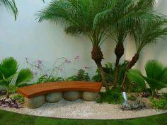 Jardin lleno de piedras blancas, palmeras y vanca de madera.