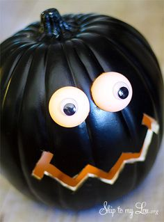 DIY: Carving pumpkin from Michaels craft store, ping pong balls, battery operated tea lights and goggly eyes. Great instructions.