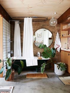 THINK TROPICAL   Spa like bathroom with tropical potted plants, a freestanding tub, and teak wood cabinets and accents