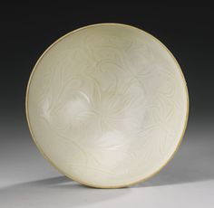 A RARE AND IMPORTANT 'DING' BOWL  NORTHERN SONG DYNASTY  北宋 ( 960-1127 )  定窯    The finely potted body of slightly rounded and steep flared form rising from a short spreading foot to an upright rim, deftly carved to the interior with scrolling leafy lotus sprays, the exterior carved and molded with three rows of overlapping upright leaves, applied overall with an even ivory-colored glaze with characteristic teardrops at the base, ..