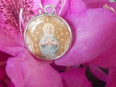 This unique, reversible pendant features a vintage holy card image of the Virgin Mary as one of her honorary titles, Star of the Sea, or Stella Maris in Latin; the other side shows an exquisite bunch of white lilies, representative of Marys purity, and taken from the same vintage holy card as the Stella Maris image. Hangs from an 18 inch black cord with lobster clasp. Perfect gift for Confirmation, Baptism, First Communion, or any occasion.