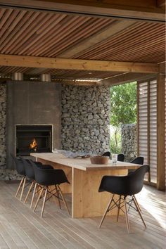 cool stone wall, vented walls, minimalist table & wood ceiling