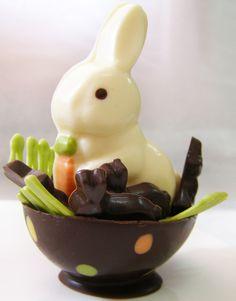 Un conejito de chocolate blanco acompañado de 8 mini conejitos de chocolate semiamargo negro en una base de medio huevo de chocolate con detalles de lunares y pasto.