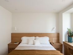 Workstead-design bedroom with custom oak headboard and built-in-bedside tables