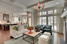 """""""The sofa placement in this space provides a visual break from the kitchen. Two chairs side by side in front of the French doors provide additional seating but don't block the view. The two smaller stools placed in front of the fireplace provide more places to sit but do not crowd the main seating area or block the view to the fireplace."""""""
