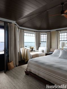 In a Shingle Style beach house in Long Island, New York, walls in the master bedroom are covered in Donghia's Silk Texture II, and the ceiling is painted in Benjamin Moore Regal Select in Night Horizon to dramatize the soaring space.