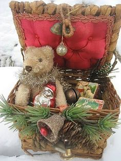 A family bear in a vintage sewing box adorned with goodies.