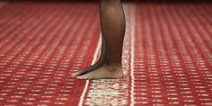 Auf einem rot-gemusterten Teppich stehen Beine in schwarzen Strumpfhosen