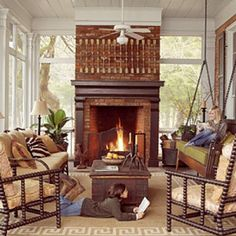 """Cozy Screened Fall Porch A wood-burning fireplace is the center of attention in this porch, and dozing, reading, and chatting are the orders of the day. An indoor-outdoor rug softens and defines the gathering space. The seating arrangement includes a upholstered swing that the homeowner had custom made based on an antique bench she saw at a Paris flea market."""