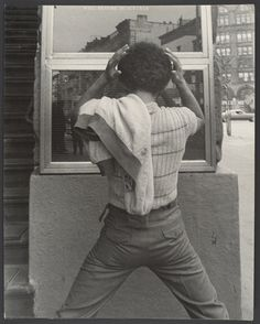 Young man fixing hair in window.  New York City, 1970's.  Leon Levinstein.