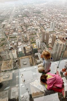 Five -year-old  Anna Kane (top) and  4-year-old Sophie Allaway check out the view from the Ledge, a new glass cube that juts out from the 103rd floor Skydeck of the Sears Tower, during a media preview July 1, 2009 in Chicago, Illinois. The 1,353 foot high observatory will open to the public tomorrow.