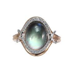 Mother of pearl creatively set below a white topaz dome with a halo of diamonds totaling .20 carats. Designed by Frederic Sage.