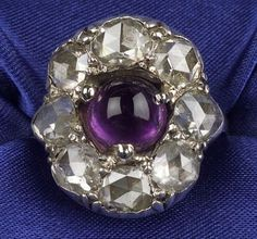 Antique Rose-cut Diamond Ring, set with eight pear and cushion shape rose-cut diamonds centering a later amethyst cabochon, silver-topped 14kt gold mount,
