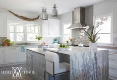 Staggered Jamie Young Lafitte 1-Light Pendant Lamps In Mercury Glass light a white kitchen island adorning long polished nickel pulls and a gray quartz countertop fixed beneath the gray quartzite waterfall countertop of the breakfast bar beside it.