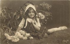 girl sits on ground, left hand holds three flowers near her breast
