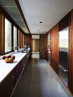 A beautiful, warm yet sleek kitchen in a home designed by the great George Nelson in the late '50s. Perhaps the floor is terrazzo, perhaps it is a highly polished linoleum. The rich wood (with the fridge and stove built in) is a nice balance to the white countertops. I like the block of colours, such as the aubergine of the cupboards below the counter.