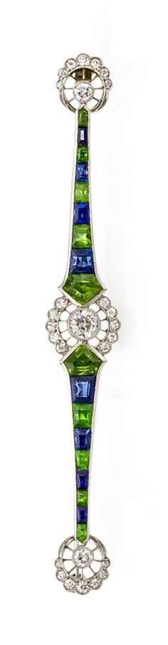 A belle époque diamond, demantoid garnet and sapphire brooch, Marcus & Co., circa 1915 designed as a tapered line of alternating calibré-cut sapphires and demantoid garnets, accentuated by three openwork circular panels of single and old European-cut diamonds; signed Marcus & Co.; mounted in platinum; width: 3in.