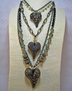 """The Easiest, Peasiest Rustic Heart Pendant. Materials and Tools:   1 package Black Premo polymer clay   Old credit card or bone folder   2"""" 20 gauge craft wire, any color   Pen or needle tool   Bead caps (I'm using Brenda Sue's Cube Drawn Beads SKU Number: cap21 and   Filigree Cone Caps SKU Number: cap18)   Gilders Paste (I'm using Bronze)   Large jump ring   Work surface – non stick sheet or a glazed ceramic tile"""