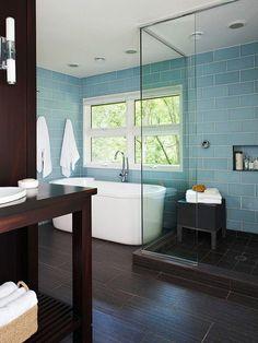 Modern Serenity--wraparound blue glass tile wall; ceiling lights; rich, dark wood floors & wall; glass stand alone shower; deep vassal tub.