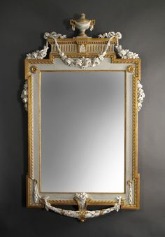 In the Manner of Johan Akerblad - A Swedish Neoclassical Painted and Parcel Gilt Mirror - Late 18th Century - The rectangular mirror plate within the beaded and ribbon-twist border with projecting corners, surmounted with a draped urn on a stepped pediment adorned with swags of roses held by ribbons, the base draped with a berry and laurel leaf garland and centered by a bracket issuing a bouquet - Dimensions: Height: 70 in, Width: 41 in. / Height: 177.8 cm, Width: 104.1 cm.
