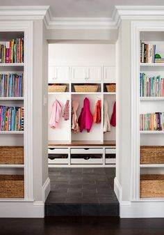 Built-in bookcases flank the doorway to a mudroom boasting a row of closed cabinets stacked over open shelving filled with wicker baskets and open lockers as well as a built-in bench over stacked shoe drawers.