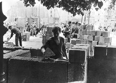 An East German worker lays some of the first blocks of the Berlin Wall 1961
