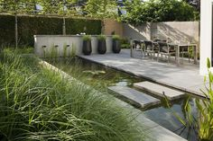 contemporary rill water feature with dining area and grasses - lovely! Hoveniersbedrijf Jan Abrahams BV