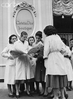 """""""A group of midinettes working in the Christian Dior House of Fashion in Paris crowd around a newspaper to read the shocking news of Dior's death in Italy"""""""