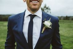 Grooms blue suit with navy blue necktie for olive and white wedding
