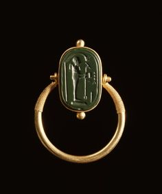 Finger Ring with a Representation of Ptah.  The ring is a moveable over pluck, which shows on one side. The standing figure of Ptah has a shrine with his name written in front of him. In the backside, the name Amun-Re is inscribed. 664-322 BC