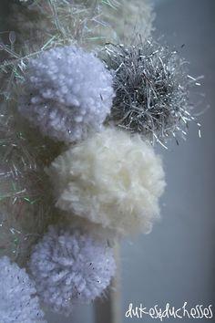 pom pom snowballs on a winter wreath - I think I need one with the silver eyelash yarn...Martha Stewart Crafts Glitter Eyelash in Sterling.