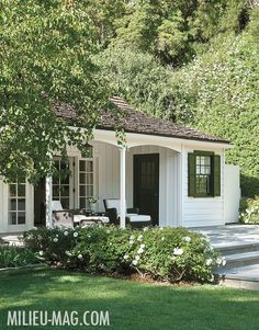 Tiny and perfect cottage with little porch and green shutters.