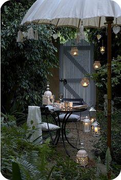 Backyard nook -- umbrella, table, lots of lanterns.