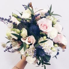A bridal bouquet full of dried lavender, dark blues and soft light roses.