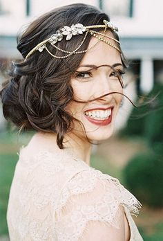 Brides.com: . A vintage-inspired headband with dangling gold chains and crystal accents.