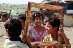 IRAQ, Diwaniyah : Iraqi children hold an empty frame at a garbage dump  where he lives in the Diwaniya village, east of the holy city of Najaf,  on August 21, 2015. AFP PHOTO / HAIDAR HAMDANI