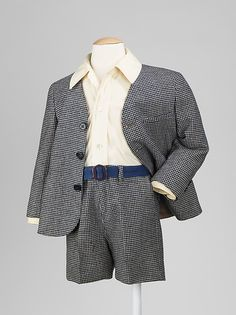 Suit - MMA  Date: ca. 1945 The suit featured here maintains the same form and construction of boy's suits from the nineteenth century, which includes interior buttons to attach the shirt to the short pants. At this time, there was no graduation from short pants to long pants as a coming of age, which was common practice in the early twentieth century. During the mid-twentieth century shorts were still an option for young boys to wear, although it was probably less common for a boy of this…