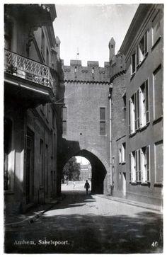 Arnhem: De Sabelspoort is een van de meest bekende punten van Arnhem. De foto is in 1938 gemaakt. In de loop der eeuwen is het bouwsel diverse malen aangepast, voor het laatst in 1642 toen de poort werd verbouwd in een mix van classistische en barokke stijl. Tussen 1829 en 1853 werden de omliggende verdedigingswerken gesloopt, maar de poort bleef staan.