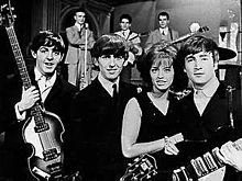 McCartney, Harrison, Swedish pop singer Lill-Babs and Lennon on the set of the Swedish television show Drop-In, 30 October 1963[60]