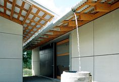 I like how this allows the water to spill freely into the rain barrel. Probably too modern, but maybe extend the gutter over the walkway and set up water catchment there?