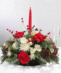 Santa Special Centerpiece: Loaded with holiday cheer, this centerpiece features today's best selection of red and white flowers and lush evergreens surrounding a taper candle. Pinecones, berries and ornaments add to the merriment.