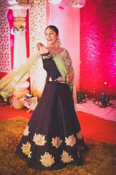Light Lehengas - Black Lehenga with Gold Bootie Embroidery at Bottom with a Lime Green Net Dupatta | WedMeGood #wedmegood #indianbride #indianwedding #black #lightlehenga #candidshot #lehenga #gold #longcholi