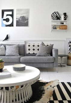 pillows. blanket on couch. couch. side table. b/w rug. via Father Rabbit's Blog.