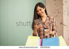 Cute Hispanic young woman carrying many shopping bags and texting on her smartphone - stock photo