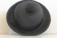 """Mid century black straw hat made by legendary French designer Jean Barthlet. It is black straw with a black cloth band around the base near the brim that cross crosses in the back. On the top is a decorative coil. Inside the circumference is lined with black grosgrain. Hat is circa 1960s.     The tag inside says Jean Barthet Junior, 107 FG SAINT HONORE PARIS and Made in France.     Measures about 10"""" across. The brim is slightly curled and approx. 2"""" wide. The inside opening that fits on the…"""